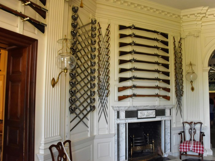 A collection of guns and swards handing in the entryway of a 18th century home