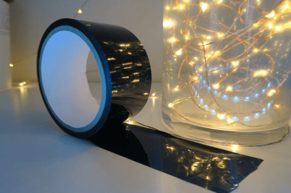 Image of the Lovehoney Bondage Tape, black with fairy lights reflected in the tape. The fairy lights are in a glass jar and the rest of the background is white.