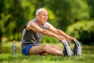 Señor haciendo estiramiento de piernas en el parque