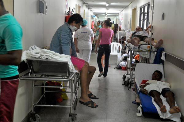 Pessoas atendidas em corredores de hospital conveniado do SUS