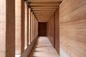 As paredes do corredor da ala dos quartos segue um padrão claro: do lado esquerdo colunas e, do direito, uma parede com portas.