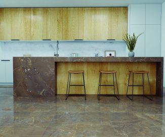 Marcado por tons terroso, o porcelanato da linha Marble Sorrento, da Roca Cerámica, é destaque no piso e bancada da cozinha.