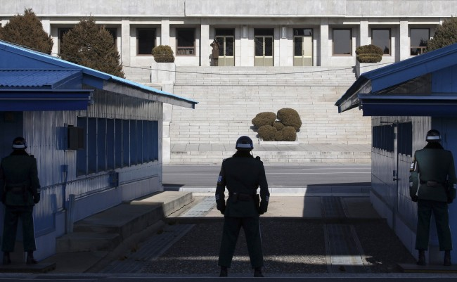 A North Korean soldier keeps watch as South Korean soldiers stand guard at the truce village of Panmunjom