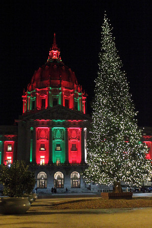 SF City Hall lit in Christmas themed lighting with the Christmas tree in Civic Center