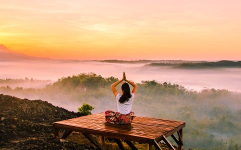 Frau meditiert hoch über den Baumwipfeln