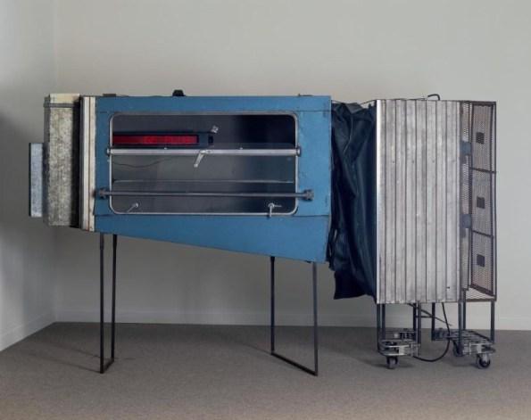 Richard Baquié (1952 - 1996)  Autrefois il prenait souvent le train pour travestir son inquiétude en lassitude 1984  Assemblage comportant : - un embout métallique - une fenêtre de compartiment de train, montée sur 2 pieds, contenant un système à diodes électro-luminescentes permettant l'affichage et le mouvement de textes - un soufflet en matière plastique - un cage grillagée dont la face est peinte en blanc, contenant 2 ventilateurs posés sur une plaque d'aggloméré recouverte de papier peint déchiré, accolée à un embout en métal ondulé ; le tout monté sur des roulettes d'un chariot de gare (dim. dans dossier)  185 x 320 x 93 cm  Transcritpion du journal lumineux : Situation du vent.../Les mots se perdent. Souvent ils ne sont que la projection de votre propre séduction.../Parfois silence.../Mes références sont dans le passé. Le monde m'appartient et m'échappe....Autrefois il prenait souvent le train pour travestir son inqiétude en lassitude.....Sinon rien....de plus....L'instant d'après...  Installation composée de 5 éléments assemblés : embout métallique, fenêtre de compartiment de train montée sur 2 pieds et contenant un système à diodes électro-luminescentes permettant l'affichage et le mouvement de textes, soufflet, cage grillagée contenant 2 ventilateurs posés sur une plaque d'aggloméré, embout en métal ondulé. L'ensemble est monté sur des roulettes d'un chariot de gare.  Achat, 1985  Numéro d'inventaire : AM 1985-181