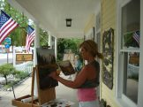 Shar Brecht and Ruth Heath painting on the porch of The Creator's Gallery