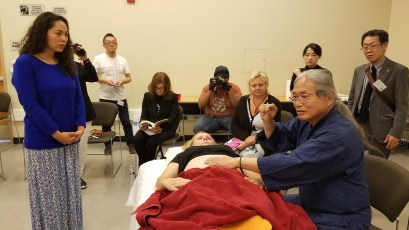 Mikio Kawasaki demonstrating during his lecture I Ching and Five Elements Treatment. This treatment starts with the abdomen to determine causes and solutions for the body's ailments. Photo taken by Jacqueline Bell Johnson.