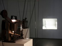 Projected on opposite walls, ever looping on 16 mm film, a person approaches a column, picks a plate and breaks it. The exposure of this multi-variant action of the break, from anger to joy, is visually linked by the exposure of the film slowly wearing away as it circles through the room between the images. I pair plate breaking and 16mm – materially fraternal twins in parallel cultural flux.