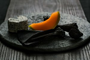 Black porcelain with surface texture formed by grazing sheep. Sheep's cheese coated in biochar, melon, carbonized sheep bones. food by Dan Barber.photograph by Andrew Scrivani