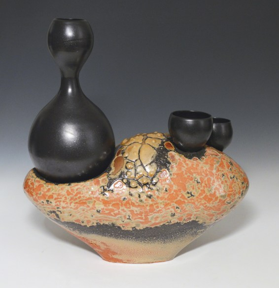 Hand–built with thrown servers, black satin and crawling shino glazes. Cone 10.