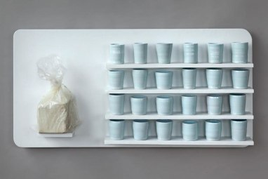 "wood panel, 25lb bag of porcelain, 25-1lb wheel thrown cups. 24""x 46""x 6"". 2010"