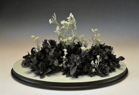 """hand formed black clay, resin, plastic flowers, wood, paint, 21"""" x 13"""" x 12"""""""
