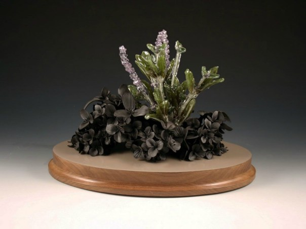 "hand formed black clay, resin dipped silk flowers, wood, paint, 14"" x 10"" x 8"""