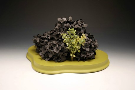 "black clay, resin, plastic flowers, wood, paint, 16"" x 10"" x 12 1/2"""