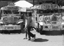 Mère et fille attendent le bus en se protégeant du soleil sous un parapluie.