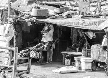 Une mère porte son enfant. Elle vit dans ce bidonville entouré d'immondices.