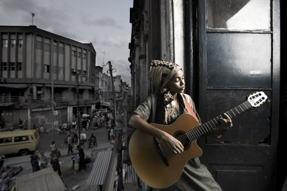 Image- Musician- Nigerian girl playing a guitar is an example of contemporary art photography