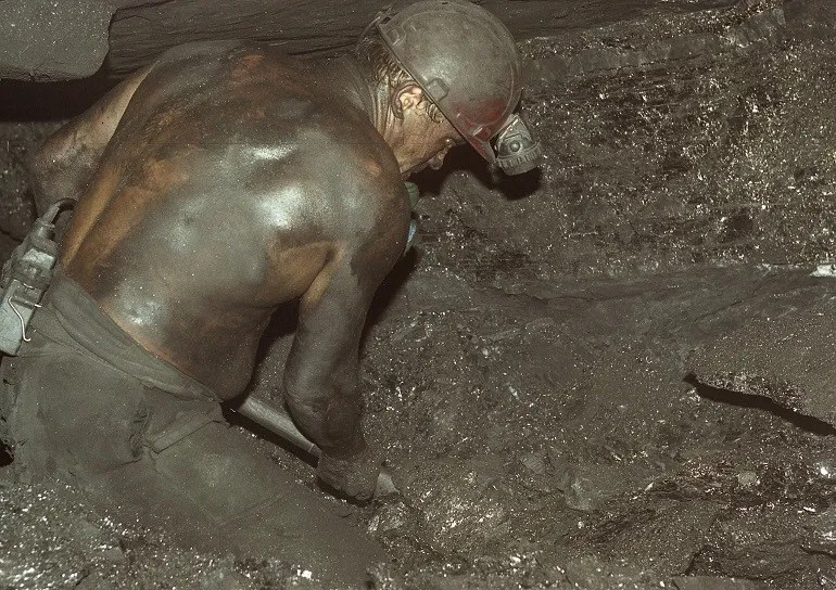 Image-Coal miner- Victor Marushchenko, Donbass – Dream Land (series) 2003, is the photograph of a Ukrainian coal miner digging himself out of the mount of coal