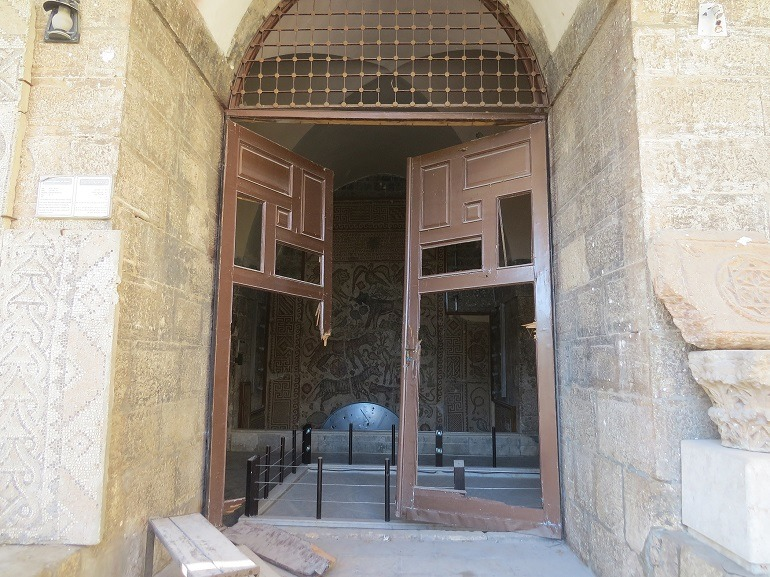 Image- Museum Door broken into pieces- Damage to the Eastern Hall of the Ma'arra Museum, Idlib Province, Syria.  Forceful entry into a museum in Syria