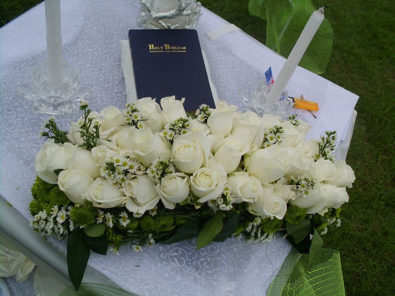 Image- The Altar with white roses, Holy  Bible and candles marked the point where the couple took their wedding vow