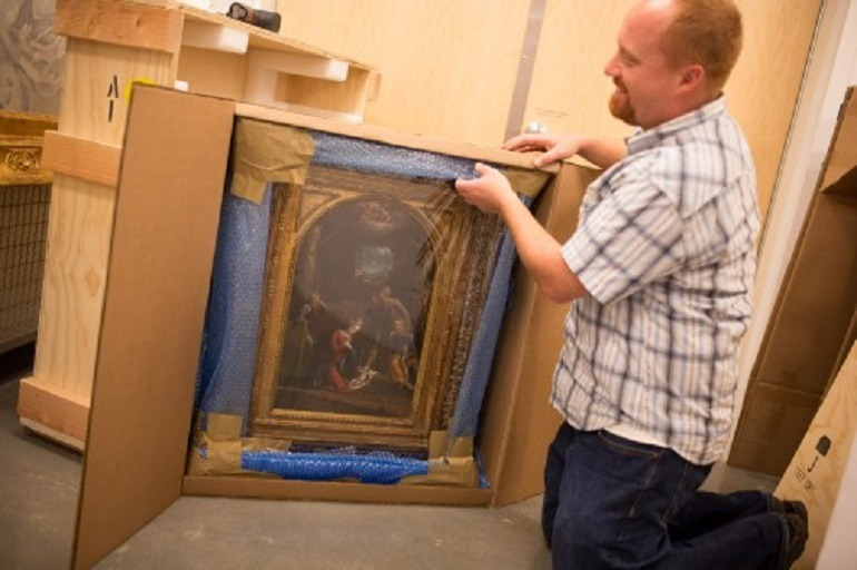 Image- Shows Chris Rupp, Westmont Museum collections manager kneeling as he carefully uncrates the Tisi painting.