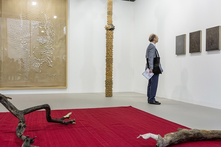 Image: An art collector examines paintings at Galerie Buchholz during Art Basel 2015-News