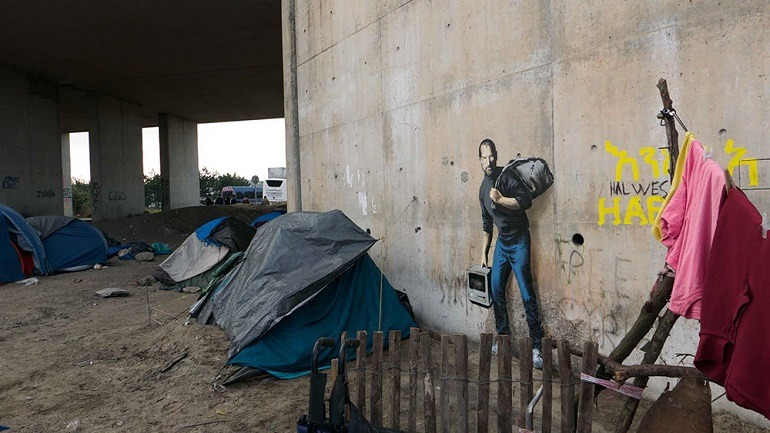 Image: Banksy, Steve Jobs. The Jungle refugee camp, Calais with tattered tents where refugees live