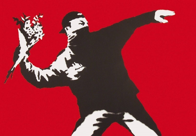 Image: Love is in the Air by Banksy, is one of the works on display in War, Capitalism & Liberty in Rome