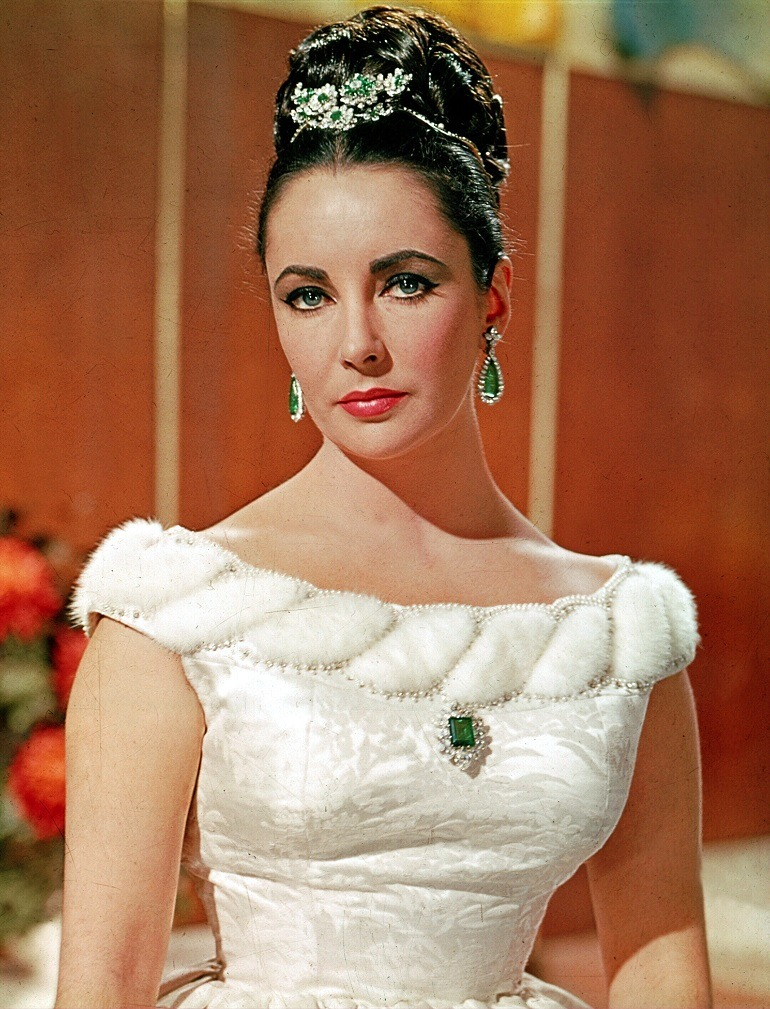 Image: Elizabeth Taylor wearing her Bulgari platinum, emerald and diamond tremblant brooch, Colombian emerald brooch and matching earrings 1963, some of the jewels on display at NGV