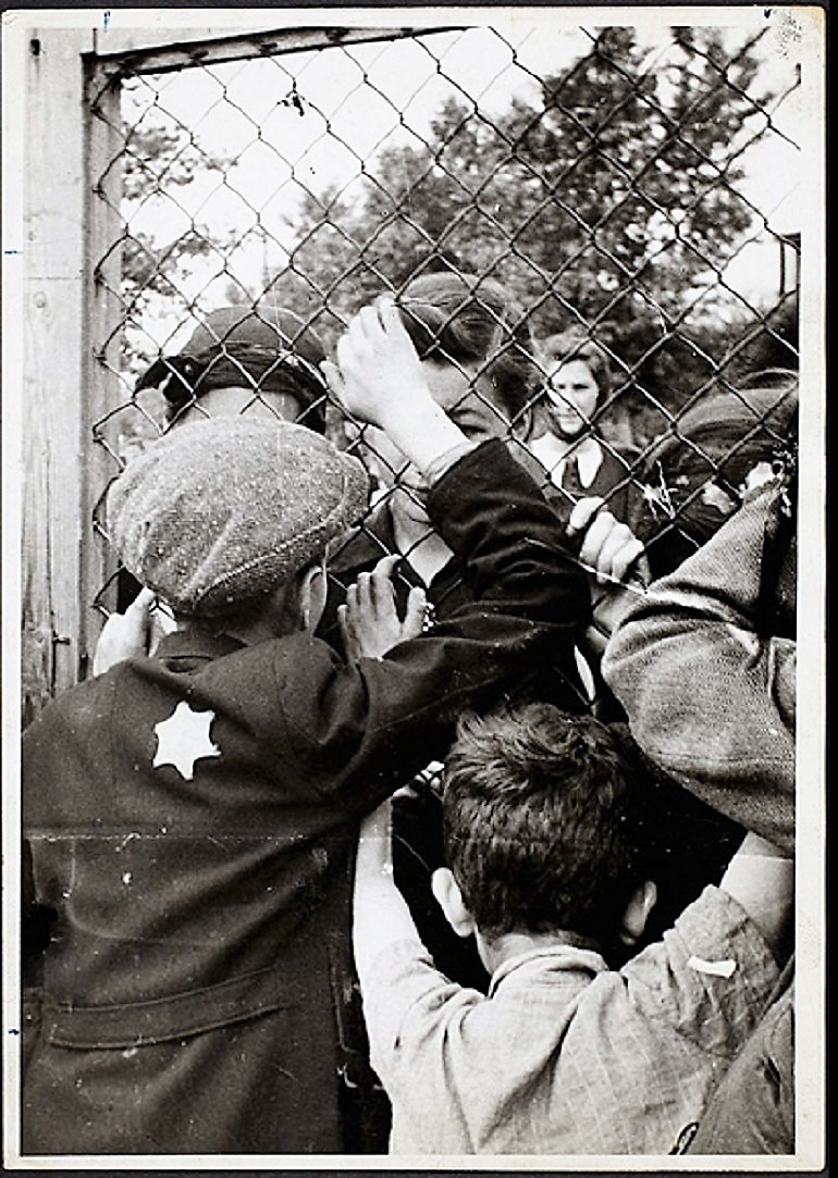 Image: Black and white photograph of Children talking through fence of central prison on Czarnecki Street prior to deportation by Henryk Ross, 1940–42