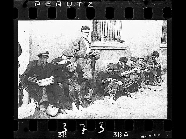 Image: Black and white photograph of Soup for Lunch, a group of men alongside building eating from pails,1940–44 by Jewish photographer Henryk Ross