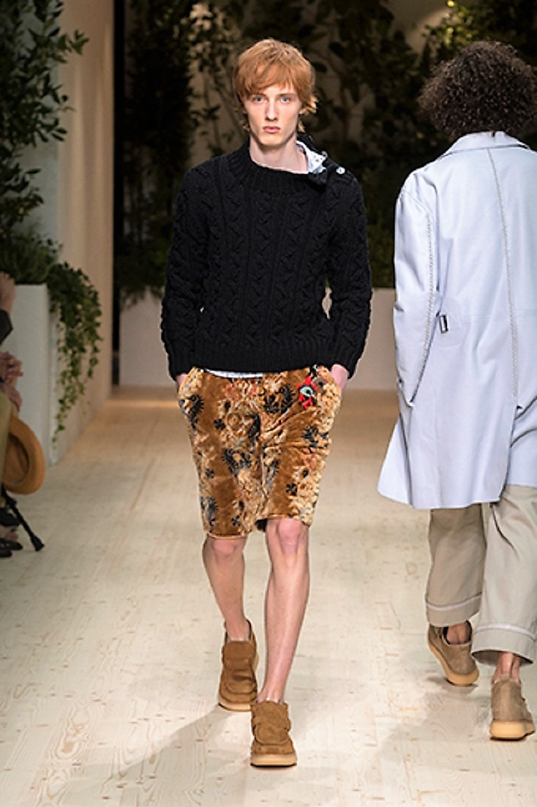 Image: A male model in flowery short and a black top on the runway during the launch of Salvatore Ferragamo Men's Spring Summer 2018 collection -04