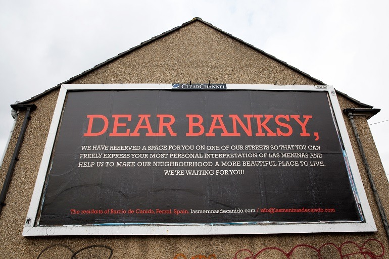 Image: A sign invites Banksy and indicates the wall where he will create his interpretation of Diego Velázquez Las Meninas during Las Meninas de Canido