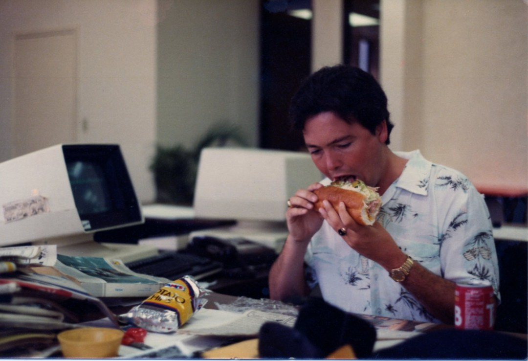 Art Coulson shoves a large sandwich in his mouth at his desk in his first newspaper office