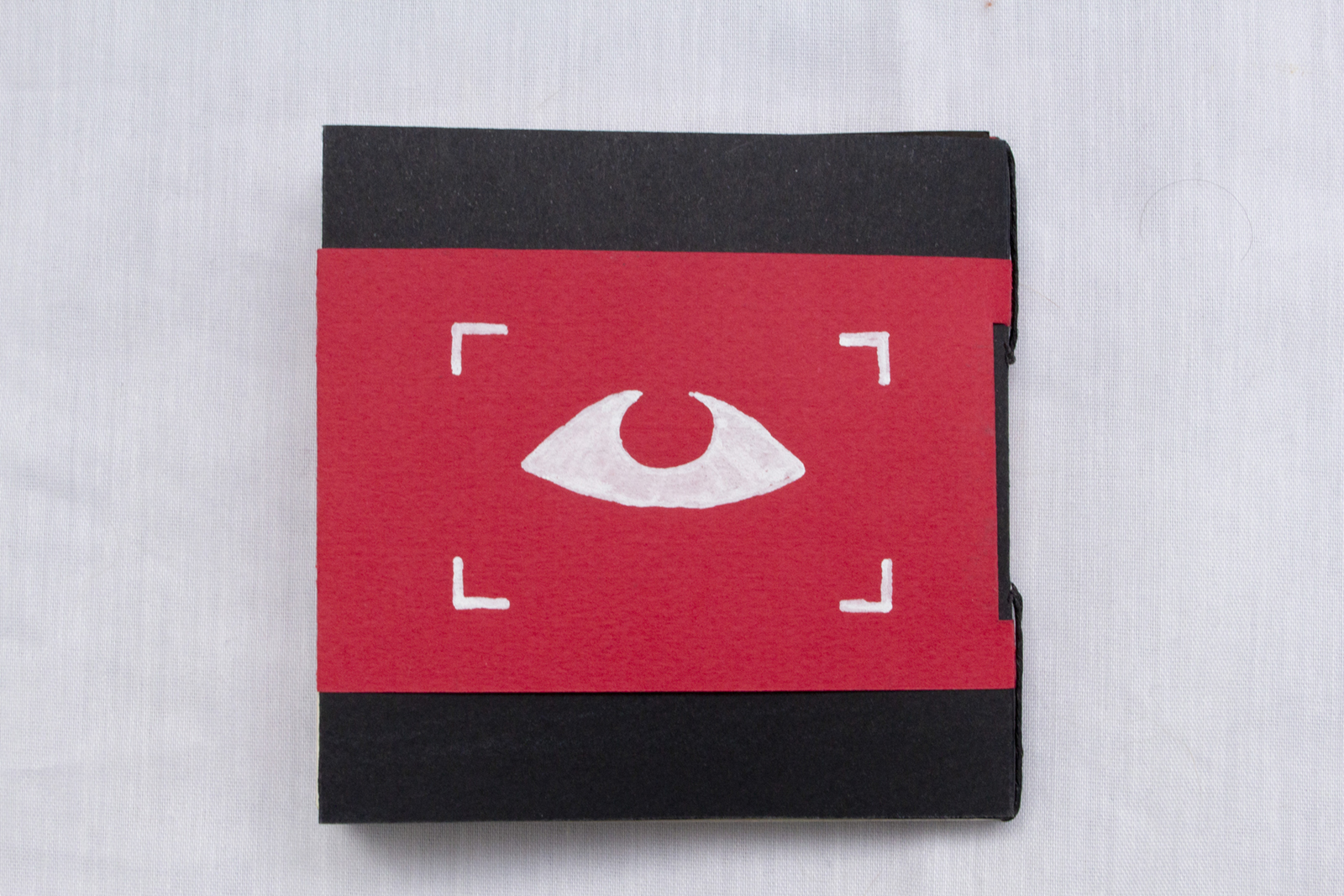 Back cover of Surveilled Self. Black paper cover with a red sleeve. Drawn on the red sleeve is a framed white eye.