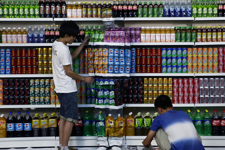 BEIJING.- Chinese artist Liu Bolin, center, is helped by his colleagues as painted to blend into rows of drinks in his artwork entitled Plasticizer, to express his speechlessness at use of plasticizer in food additives, in his studio at the 798 Art District in Beijing, China, Wednesday, Aug. 10, 2011. AP Photo.
