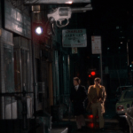 Mean Streets (1973) | Martin Scorsese production design | Martin Scorsese Films | Robert DeNiro and Harvey Keitel on the streets of New York with large gun sign as foreshadowing