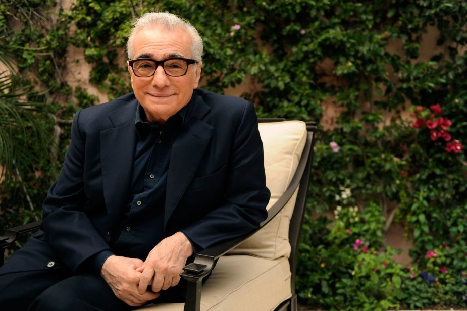 Martin Scorsese production design   Martin Scorsese Films   Director Martin Scorsese sitting in metal chair with white cushions in front of greenery in navy suit with glasses