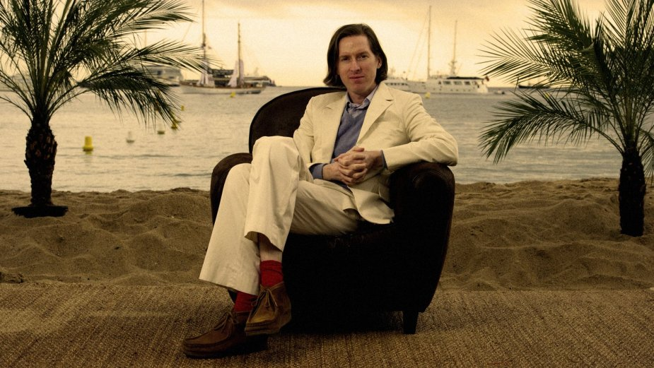 Director Wes Anderson sits in chair on beach