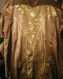 Golden pattern on satin fabric. Fragment
