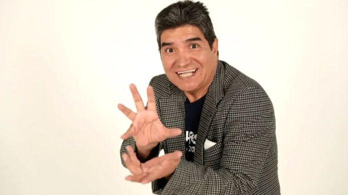 Ricardo Silva, cantante de Chala Head Chala, la canción de Dragon Ball Z, posando con una sonrisa y un traje gris sobre un fondo blanco.