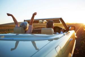 Fotografía de una pareja mayor manejando un auto vintage en el atardecer