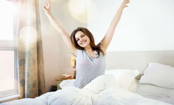 mujer contenta en la cama - inmuebles con renta