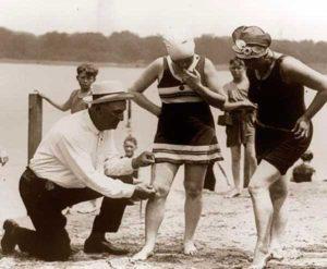 Patrulheiros na praia medindo o comprimento de trajes de banho das mulheres na década de 1920.