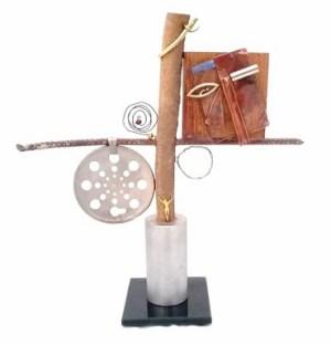 Claudia Seber. Entre a Cruz e a Espada (2019) -36 x 34 x 5 cm (vidro;ferro;pino de pistão;tronco de madeira;cobre;latão;prata;pedras;ralo;espelho) R$ 400,00