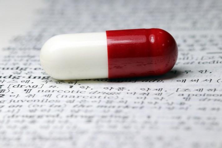Pílula de remédio apoiada sobre uma bula
