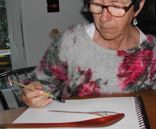 l'aquarelliste, cécile van espen, peint une cuillère de bois qui est en premier plan. puis vient le bloc de dessin, puis cécile van espen. dans sa main droite, elle tient un pinceau à réserve d'eau