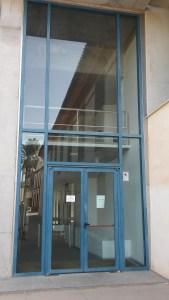 Puerta metálica de acceso principal al IAPH, desde la zona del ombú y el arco de legos