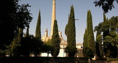 Vista de la Cúpula de la Iglesia y de la gran chimenea del Monasterio de la Cartuja de la huerta. Se ve el paseo de cipreses en primer plano